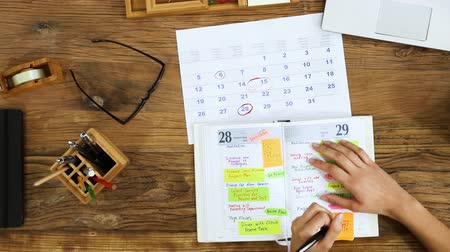 Elevated View Of A Businessperson Planning Agenda In Business Diary At Workplace