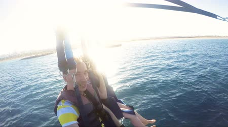 Smiling Couple Waving Hello Hands While Parasailing Over The Idyllic Sea Wideo