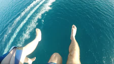 View Of Couples Feet Parasailing With The Speed Boat On The Sea