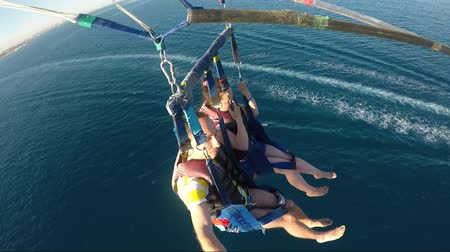Happy Couple Enjoying The Parasailing Over The Blue Sea
