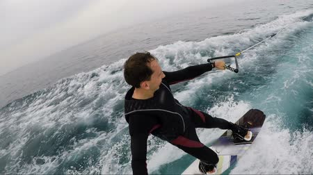 Happy Man Enjoying The Wakeboarding In Wetsuit Over The Sea