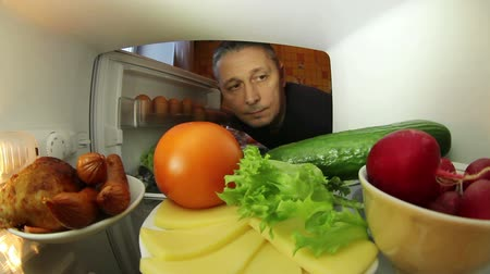 lodówka : Man looking for food in the fridge .The choice between meat or vegetables.Filmed from the inside of the refrigerator .