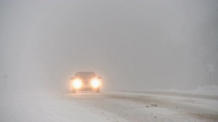 arado : Winter snowstorm on highway.Cars driving through the snow.