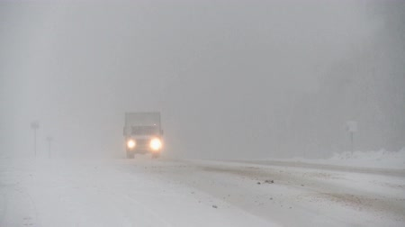 フィンランド : Winter snowstorm on highway.Cars driving through the snow.
