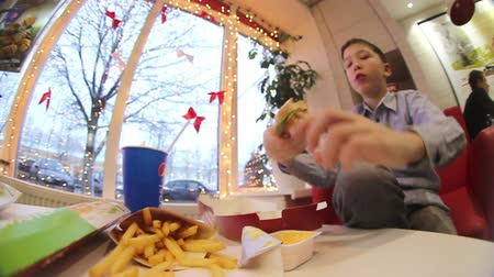 hranolky : Boy eating a hamburger and fries at the cafe.American food. Dostupné videozáznamy