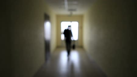 passagem : The silhouette of a man goes through the dark corridor . The Ghost of a businessman .The path to success.