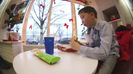 fast food : Boy eating a hamburger and fries at the cafe. Stok Video