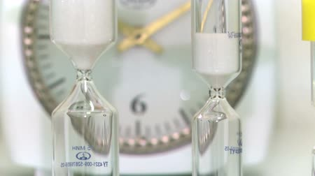 kuvars : Hourglass in colorful flasks on a background of quartz.. Stok Video