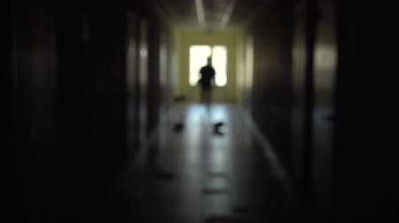 dismissal : Silhouette of a man runs through the dark corridor. Stock Footage