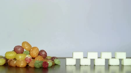 fructose : Colorful candies and white sugar.