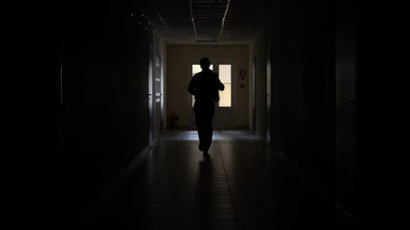 sahte : Slow motion. Silhouette of a man runs through the dark corridor. Dismissal.The Ghost of a businessman .