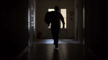discomfort : Slow motion. Silhouette of a man runs through the dark corridor. Dismissal.The Ghost of a businessman .