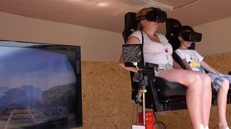 megijeszt : Woman and child on the virtual reality ride using gear VR headset.