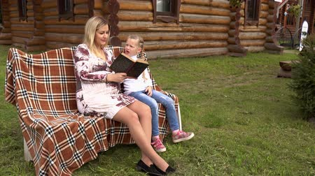 ubrania : Mom shows the child the book on the background of a country house.