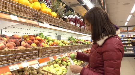 koszyk zakupy : Woman in supermarket selects fruit and vegetables. Wideo