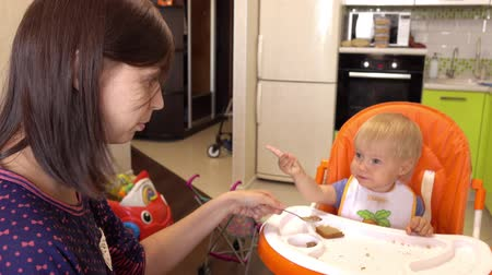 encantador : Mother gives food to her adorable child at home. Stock Footage