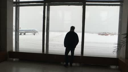 looking for : Silhouette of a man at the airport.Man comes and looks in a terminal window.