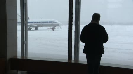 looking forward : Silhouette of a man at the airport.Man comes and looks in a terminal window.
