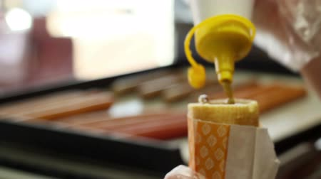 mustard : A woman prepares hot dog by adding ketchup , mustard and hotdogs in fast food diner.