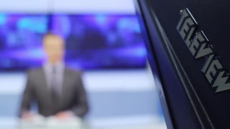 muhabir : Male silhouette of the presenter reads on a teleprompter.TV studio.