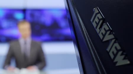 briefing : Male silhouette of the presenter reads on a teleprompter.TV studio.