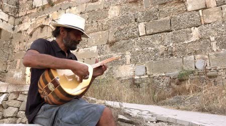 isztambul : A street musician plays a Turkish instrument. A man in a white hat plays a game of baglama.