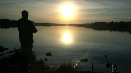 fisher : Slow motion. Silhouette of a fisherman at sunset. Fishing on the lake. hobby.