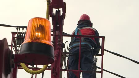 replace : The electrician connects the cables on the electrical support, in the foreground of the light rotation in focus.The worker stands on the crane fixing the high-voltage electric line. Stock Footage