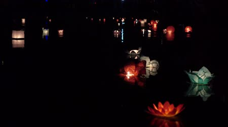 lanterna : Festival of lanterns on the water. Water lantern in the shape of a Lotus with a candle flame floating at night on the water.