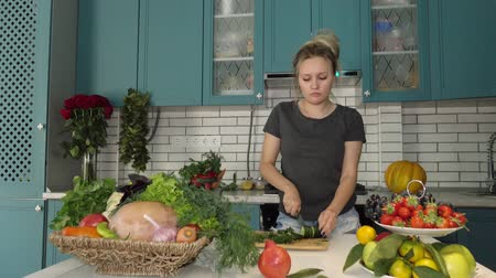 вегетарианство : The girl is preparing healthy food in the kitchen with vegetables. Vegetarian cuisine. A young Caucasian in his twenties. Стоковые видеозаписи