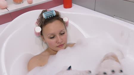 çekicilik : Portrait of a girl in a curler, lying in the bathroom. She listens to music and sings. White bubble bath. Stok Video