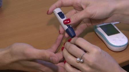 glukometr : Diabetic puncture the finger to measure the level of sugar in blood close-up. Measuring the level of glucose in the blood. Wideo