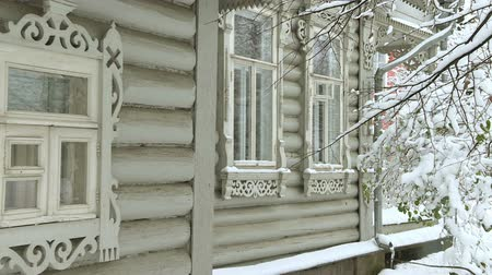 esculpida : Window of a wooden house. Branches of trees, covered with snow . Vídeos