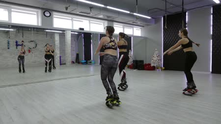 A female group of three young, sexy girls Kangoo Jumps in the gym.