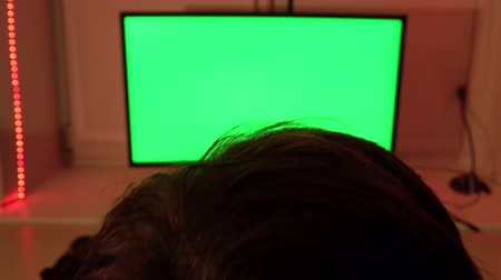 kütük : A teenager in a red chair in front of a green computer screen.