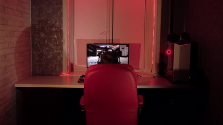 esports : Teenager playing on the computer.The room has colorful neon led lights.Gambling addiction.
