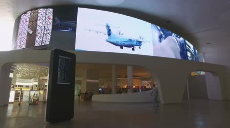 departure : camera moves through the airport departure hall with large media screen