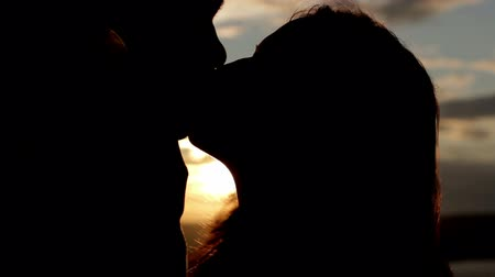 beijos : lovers kissing in a sunset on a river - silhouette HD