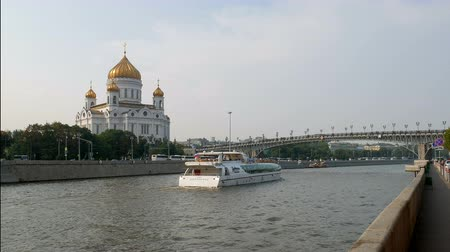 plated : white pleasure boat floating on Moscow river to Patriarshy Bridge, near church