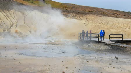 fumaroles : tourists are strolling on geothermal area Seltun in Iceland, white steam is going up of area