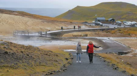 fumaroles : two blonde women are walking and looking to a side in geothermal area Krysuvik in Iceland Stock Footage