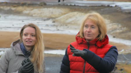 seltun : close up shooting of two blonde tourists, smiling and walking in geothermal area Krysuvik in Iceland