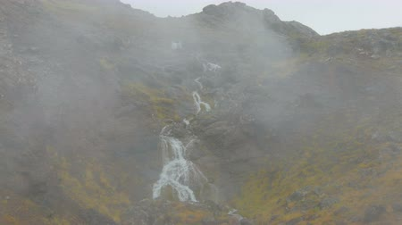 seltun : water is falling from top of mountain in Iceland, white steam is going up from area Krysuvik Stock Footage