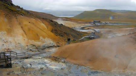 fumaroles : tourists are strolling in Seltun, Krysuvik in Iceland in cloudy wet weather,drop of rain in a camera