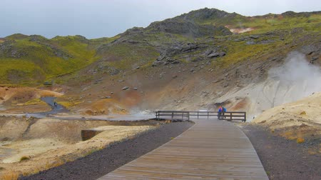 fumaroles : wooden runway in geothermal area Seltun in Iceland in rainy weather, tourists are walking