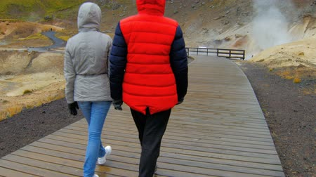 fumaroles : wooden runway in geothermal area Krysuvik in rainy weather, two tourists are walking through frame Stock Footage