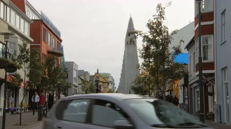 hallgrimskirkja : Reykjavik, Iceland - SEP, 2016: view of church Hallgrimskirkja and street in capital Reykjavik, Iceland, cars are moving, people are strolling Stock Footage