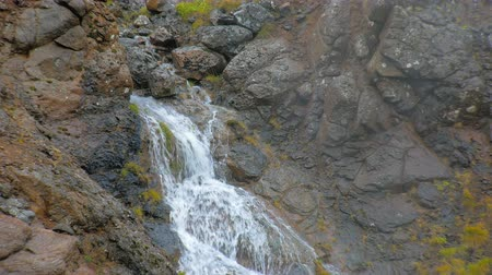 seltun : close up of flow of small icelandic waterfall, water flows from rocks, white steam rises