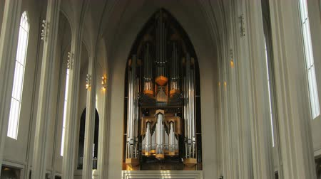 catholic cathedral : view inside catholic church, organ, narrow columns and windows, daylight is lying on walls