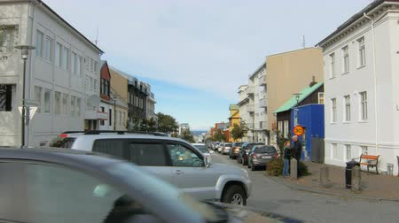hallgrimskirkja : Reykjavik, Iceland - SEP 26, 2016: people with dogs are walking on Skolavordustigur street in Reykjavik, cars are moving on a road, Atlantic ocean is on background, sunny day Stock Footage